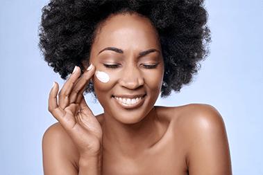Mulher preta cuidando de sua pele com produtos Sisley Paris